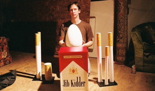 Artist posing with cigarette sculptures back stage in Portland Oregon, 2012. Picture by Brian Echon